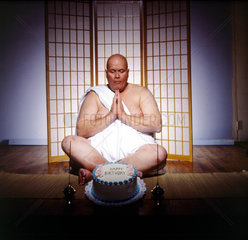 Mann meditiert vor Geburtstagstorte