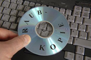 Hand haelt CD mit Aufschrift 'Raubkopie'