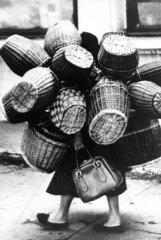 Frau transportiert 10 Koerbe