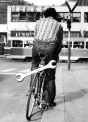 Mann mit Schraubenschluessel auf Fahrrad