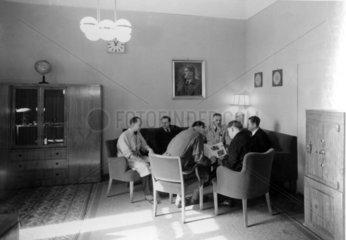 deutsche Maenner im Wohnzimmer mit Hitlerportrait an der Wand