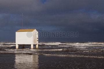 Tides and stilt building on beach