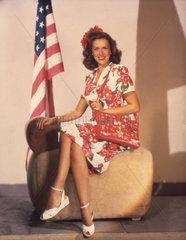 Frau mit Tasche sitzt neben US Fahne