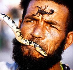 Mann mit Schlange und Skorpion im Gesicht
