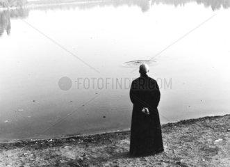 Moench mit Heiligenschein steht am See