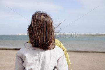 Girl looking at ocean  rear view