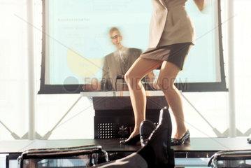 Frau tanzt auf Schreibtisch