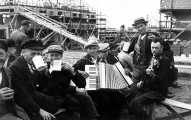 Bauarbeiter feiern mit Bier und Musik 1920