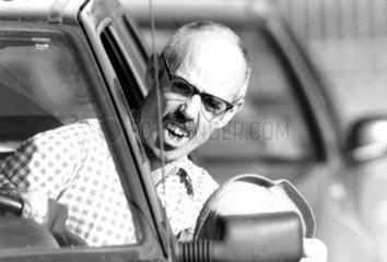 Mann schimpft aus Auto