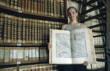 Frau steht in alter Bibliothek