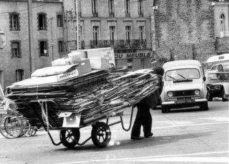 Mann zieht ueberladenen Wagen
