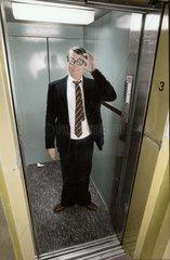 Mann im Anzug steht im Fahrstuhl