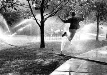 Mann springt weg vom Rasensprenger