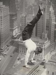 Mann macht Handstand auf der Br_stung eines Hochhausdaches