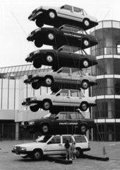 Kinder stehen vor Turm aus Autos
