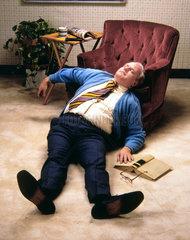 Mann schlaeft im Wohnzimmer