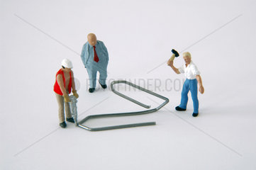 zwei Bauarbeiter bearbeiten eine Bueroklammer
