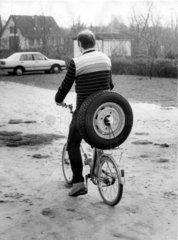 Fahrradfahrer transportiert Autoreifen