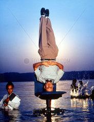 Mann macht Kopfstand auf Buerostuhl im Wasser