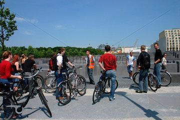 ein Reisefuehrer mit eine Gruppe Fahrradfahrer Touristen am Holocaust Mahnmal
