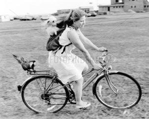 Frau mit Hund und Vogel auf Fahrrad