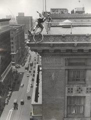 Mann f_hrt Fahrrad auf Hochhausdach