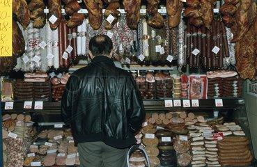 Markthalle - Mann steht vor Wurststand