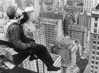 Steel worker sitting on a girder having a d