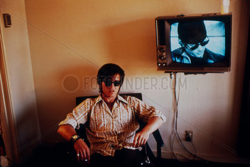 Man sitting beside a wall-mounted television screen  United States  1971.