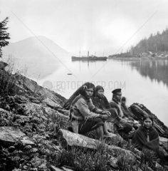 Amerindian family sitting beside a waterway  Alaska  USA  c 1868.
