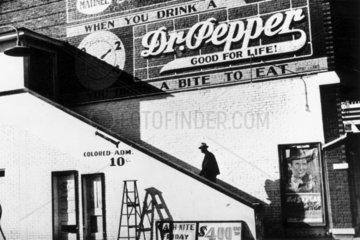 A black man entering a movie theatre's 'coloured' entrance  USA  October 1939.
