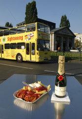 Currywurst und Sektflasche mit vorbeifahrendem Reisebus