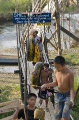 Touristen auf dem Rueckweg vom Tubing auf der Bruecke ueber den Nam Xong /