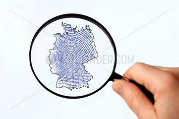 Lupe ueber dem Umriss von Deutschland mit einem Fingerabdruck