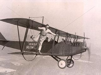 Mann auf Tragfl_che eines fliegenden Flugzeugs