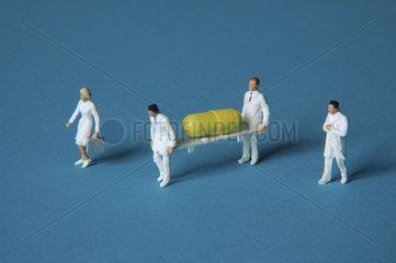 Figuren tragen Krankentrage mit Tablette