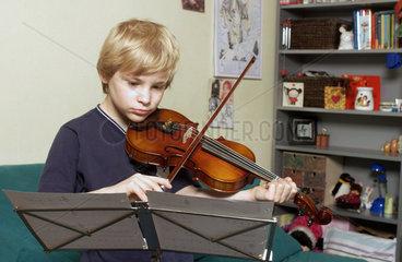Junge beim ueben mit der Geige
