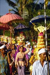 Prozession mit Opfergaben und Flaggen auf Bali