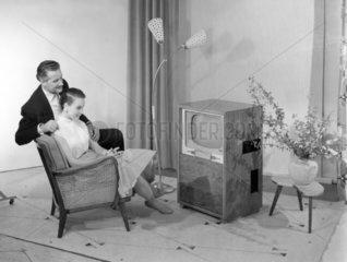 Frau und Mann im Sessel vor Fernsehapparat