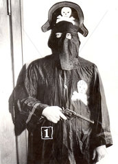 Mann als Pirat verkleidet mit Maske und Pistole