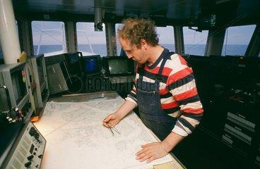 Arbeiten an Bord eines deutschen Fischtrawlers im Atlantik - Kapitaen und Inhaber berechnet die besten Fanggebiete
