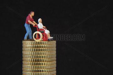 Figur im Rollstuhl steht auf einem Stapel Muenzen