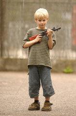 kleiner Junge spielt mit Spielzeugwaffe
