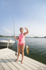 Caucasian young girl 10-13 years wearing a pink swimsuit shows the fish she caught from the dock on Ten Mile Lake  Minnesota  United States of America  North America