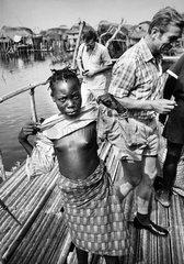 afrikanisches Maedchen hebt ihr Shirt hoch und zeigt ihre Brueste