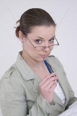 Frau mit Brille und Kugelschreiber denkt nach