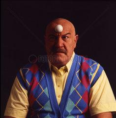 Mann mit Ball auf dem Kopf