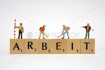 Arbeiterfiguren auf Scrabble-Spiel