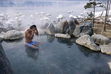 Man taking a bath in an onsen near a lake Japan