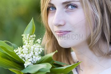 Teenage girl holding a bouquet of lily in his hands